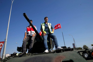 Men sit atop a military vehicle in front of Sabiha Airport, in Istanbul