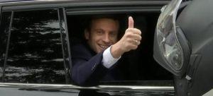 Emmanuel Macron veifar til vegfarenda í París.