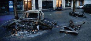 Brennt bilhræ á götum Parísar eftir átök lögreglu og grænvestunga laugardaginn 1. desember.