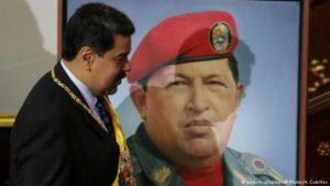 Nicolas Maduro við mynd af Hugo Chaves, forvera sínum og leiðtoga.